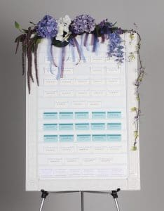 wedding celebration board version of name badge organizer with flower decorations on top
