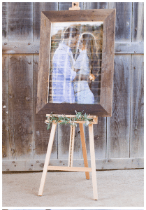 wedding celebration name badge display board with barn wood trim and happy couple embracing