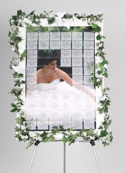 celebration seating board with bride in dress partially revealed by some name tags on celebration board