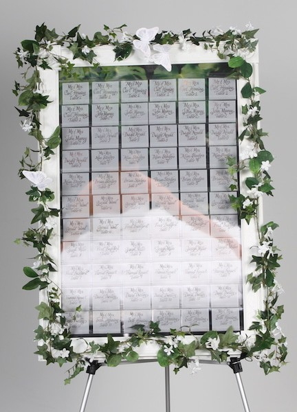 celebration seating board with transparent name tags show bride in dress on background of celebration board