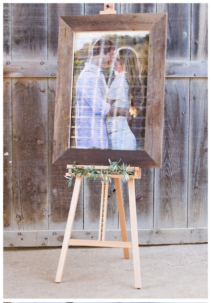 wedding celebration seating board with barn wood trim and print of happy couple embracing on background of celebration board